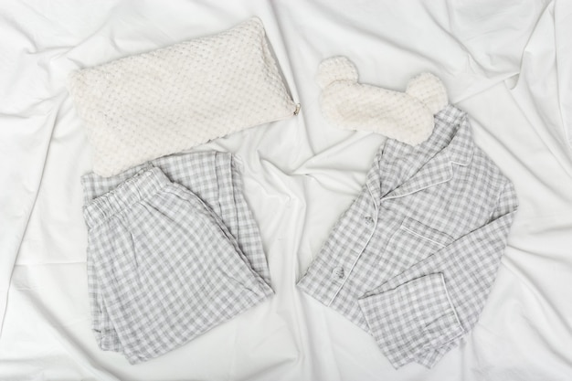 Pigiama grigio, maschera per dormire, soffice cuscino soffice su un lenzuolo sgualcito bianco.