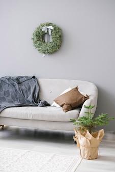 Divano grigio con coperte e cuscini nel soggiorno in stile scandinavo
