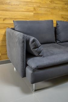Divano grigio con cuscini intorno a una parete di legno su un pavimento grigio