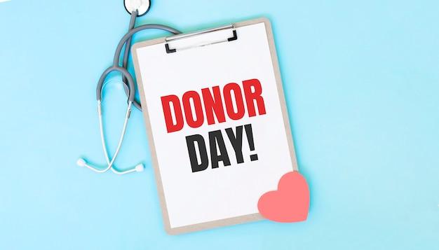 Stetoscopio grigio e piatto di carta con un foglio di carta bianca con testo donor day backround azzurro.