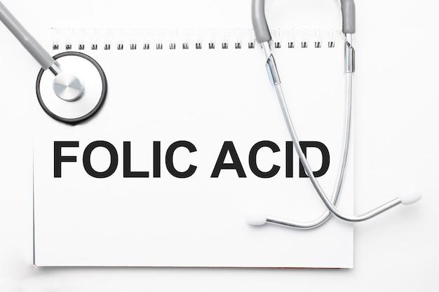 Stetoscopio grigio e piatto di carta con un foglio di carta bianca con testo acido folico backround azzurro. concetto medico.