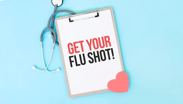 Stetoscopio grigio e piatto di carta con un foglio di carta bianca con il testo get your flu shot sfondo azzurro. concetto medico.
