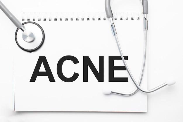 Stetoscopio grigio e piatto di carta con un foglio di carta bianca con testo hernia sfondo azzurro. concetto medico.