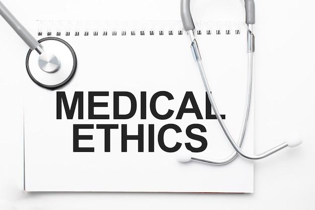 Stetoscopio grigio e piatto di carta con un foglio di carta bianca con backround azzurro di testo etica medica. concetto medico.
