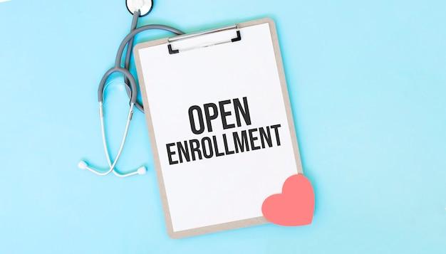 Stetoscopio grigio e piatto di carta con un foglio di carta bianca con il testo aperto enrollment backround azzurro