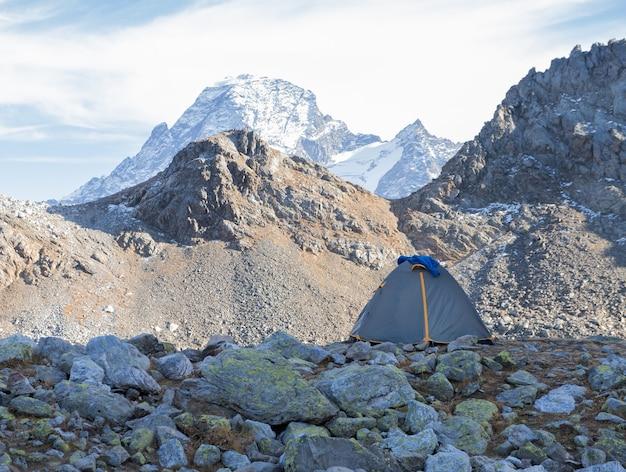 Tenda grigia sullo sfondo del paesaggio di alta montagna