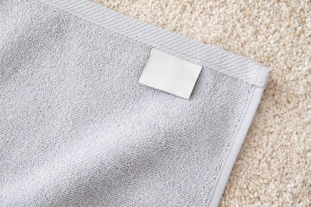 Asciugamano in spugna grigio con etichetta vuota bianca sul tappeto in pile beige.
