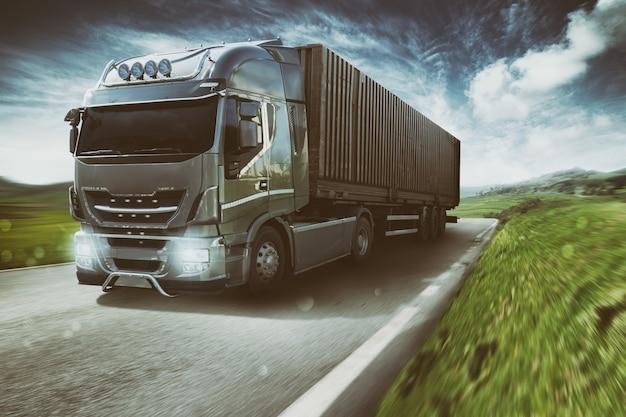Camion grigio che si muove velocemente sulla strada in un paesaggio naturale con cielo nuvoloso