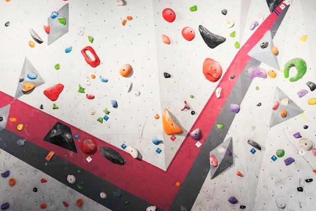 Muro grigio con prese di arrampicata in palestra. concetto di arrampicata su roccia.