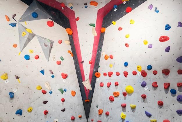 Muro grigio con prese d'arrampicata e corde in palestra. concetto di arrampicata su roccia.