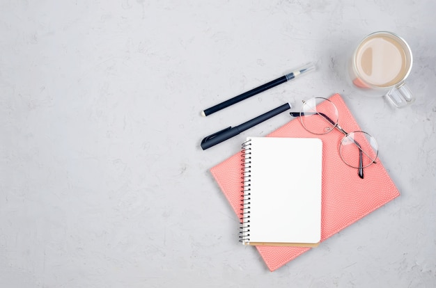 Tavolo scrivania grigio sul posto di lavoro con notebook, vuoto vuoto, forniture, bicchieri e tazza di caffè