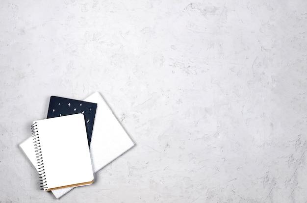 Tavolo scrivania da lavoro grigio con notebook, spazio vuoto vuoto, forniture e bicchieri.
