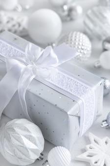 Grey wrapped presente con un fiocco bianco e decorazioni di natale bianco e argento closeup. composizione invernale con carta etichetta vuota, mockup, spazio copia