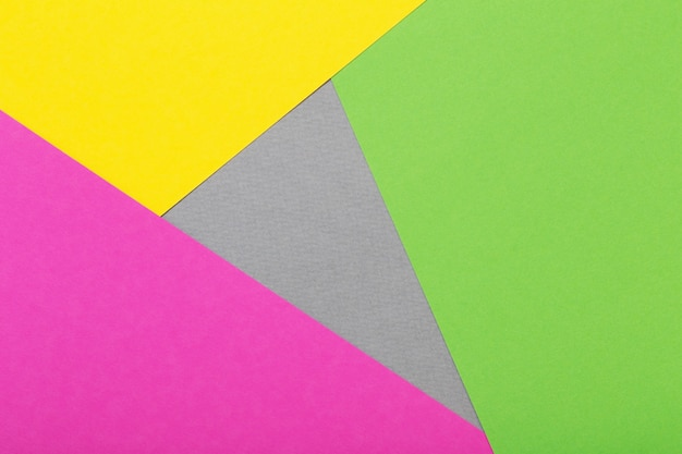 Fondo geometrico dei fogli di cartone grigio, giallo e verde e rosa