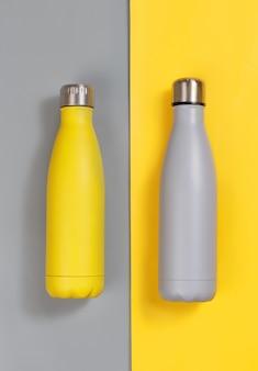 Bottiglie riutilizzabili isolate grigie e gialle su sfondo grigio e giallo vista dall'alto