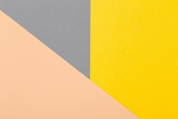 Fondo geometrico dei fogli di cartone grigio, giallo e beige chiaro