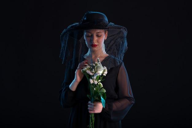 Donna in lutto vestita di nero con fiori su superficie nera isolata morte funerale