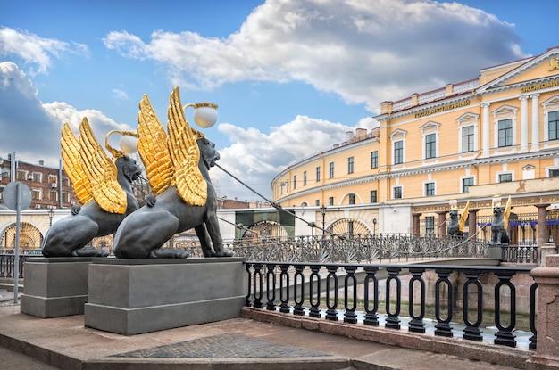 Grifoni con ali dorate sul ponte della banca a san pietroburgo e l'università statale di economia
