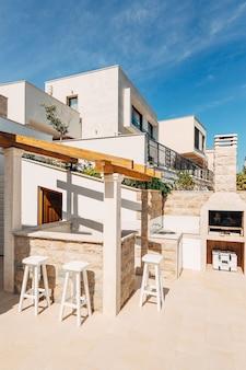 Zona grill nella villa in riva al mare un ampio cortile con una griglia in pietra e una pietra bianca aperta