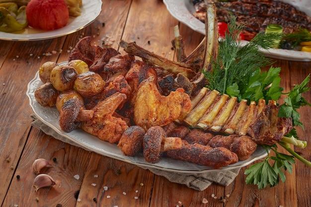 Grill barbecue assortiti, sullo sfondo di legno