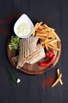 Sandwich di pollo alla griglia con patatine fritte e piccante su fondo di legno