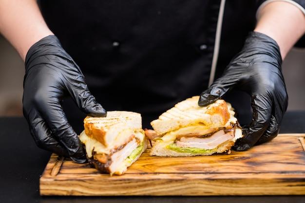 Menu del ristorante alla griglia. primo piano delle mani dello chef che servono sandwich di petto di tacchino affumicato su tavola di legno.