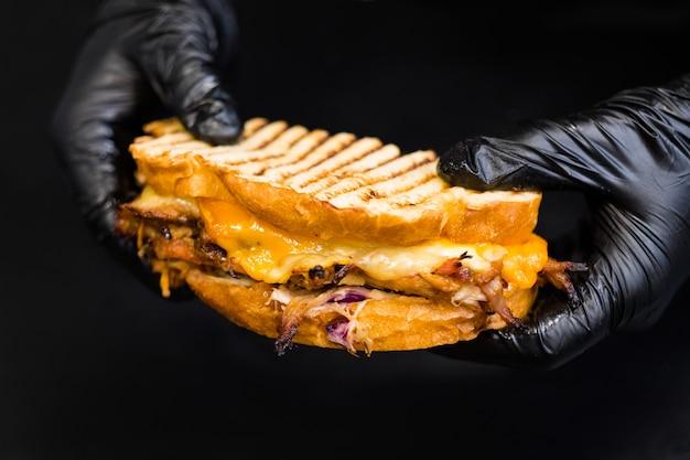 Menu del ristorante alla griglia. primo piano del panino di maiale tirato con pane rustico, cipolla caramellata e formaggio.