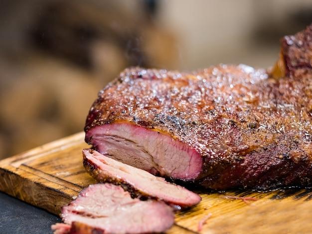 Menu del ristorante alla griglia. petto di manzo affumicato caldo sul bordo di legno rustico.
