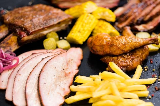 Menu del ristorante alla griglia. carne arrosto, assortimento di pollame, patatine fritte, mais bonduelle al forno.