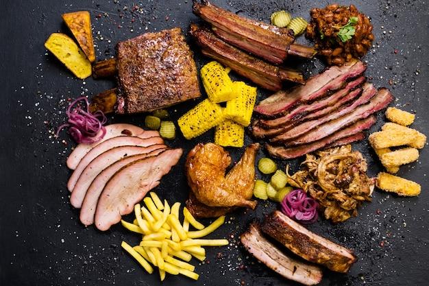Menu del ristorante alla griglia. vista dall'alto di fette di manzo affumicato, carne di maiale, assortimento di pollame arrosto e piatti di verdure.