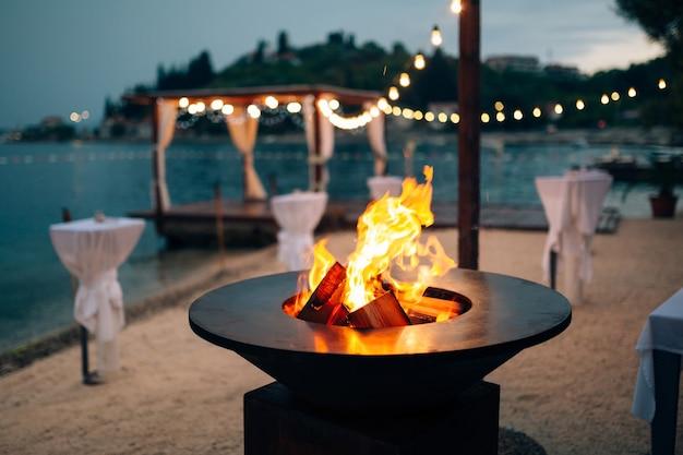 Griglia con fiamme all'interno del piano cottura tondo sulla spiaggia sullo sfondo del gazebo di
