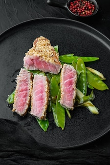 Set di bistecca di tonno ahi alla griglia con cipollotti e piselli dolci allo zucchero, su piastra, su sfondo di pietra nera