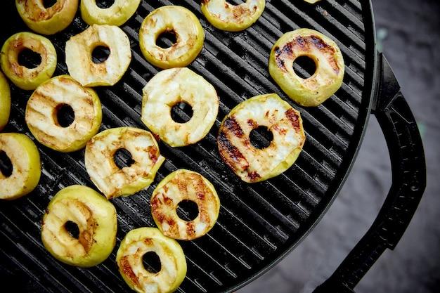 Mele grigliate sulla griglia a gas nero. dessert alla griglia.