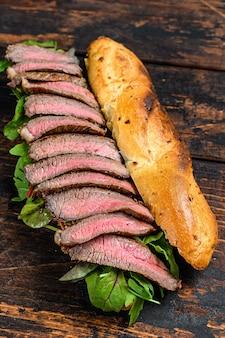 Sandwich di bistecca baguette alla griglia con rucola e formaggio. fondo in legno scuro. vista dall'alto.