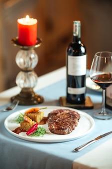 Bistecca di ribeye di manzo alla griglia con patate sulla piastra bianca con vino rosso