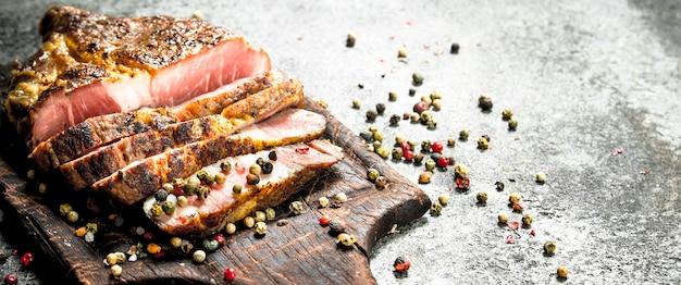 Bistecca di manzo alla griglia su una lavagna con spezie. su fondo rustico.
