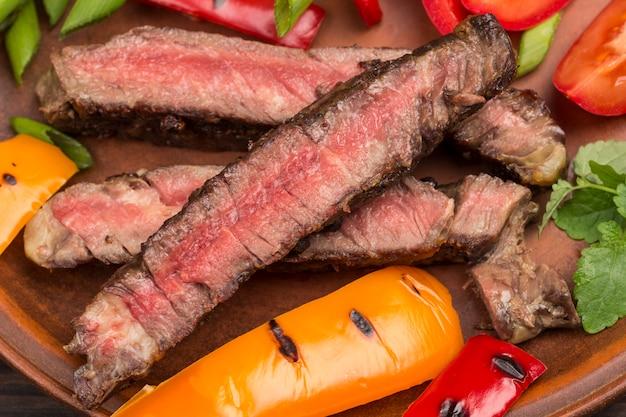 Bistecca di manzo alla griglia, tagliata a pezzi con peperone rosso e giallo. avvicinamento. fonte naturale di proteine.