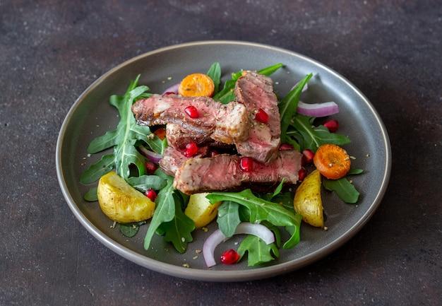 Bistecca di manzo alla griglia con insalata di rucola, patate, carote, cipolle e melograno. mangiare sano. dieta.