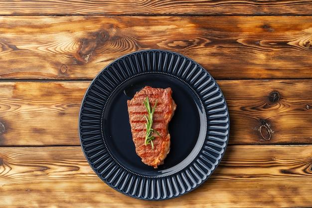 Bistecca di manzo alla griglia servita sul piatto blu sul tavolo