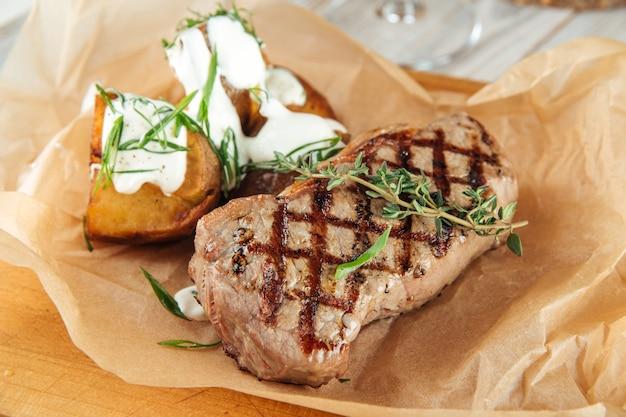 Bistecca di manzo alla griglia con patate sulla tavola di legno