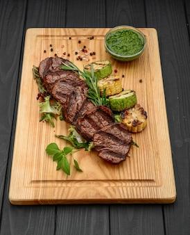 Bistecche di manzo alla griglia sul tagliere - preparazione della cena, pesto