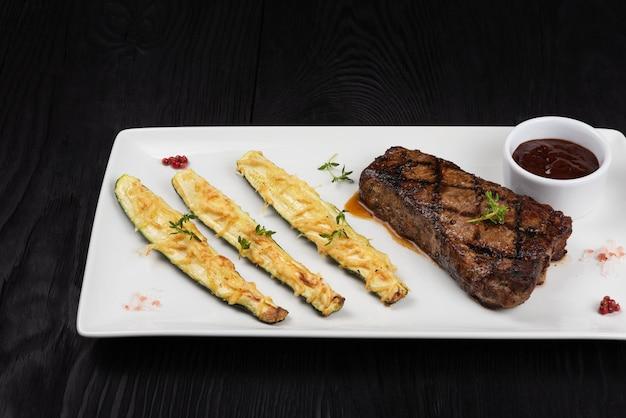 Bistecca di lombata new york di black angus alla griglia con zucchine su piatto bianco su sfondo di legno nero...