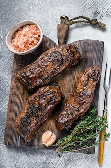 Bistecche di petto alla griglia in salsa barbecue su una tavola di legno.