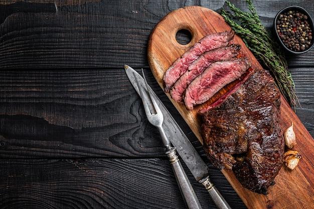 Grilled butchers scelta bistecca onglet hanging tenera carne di manzo su un tagliere. tavolo in legno nero. vista dall'alto.