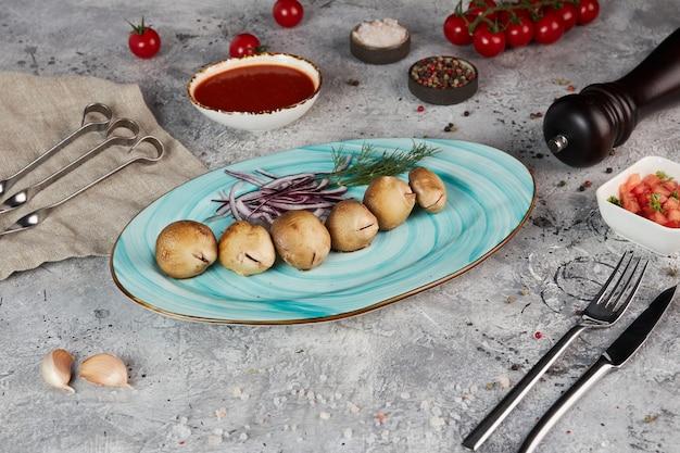 Funghi prataioli alla griglia con cipolle rosse su un piatto