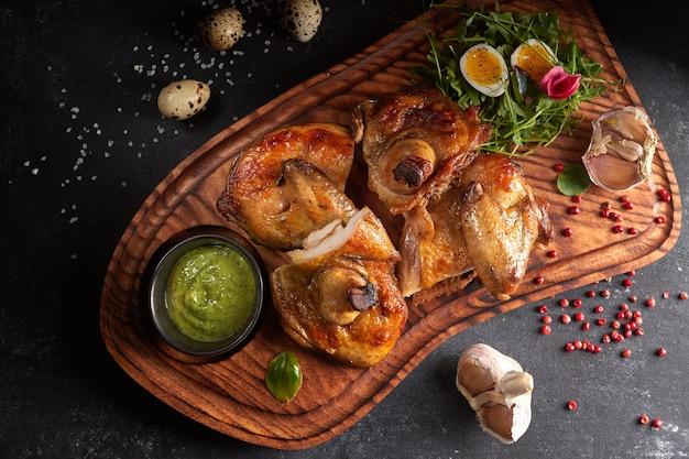Pulcino alla griglia con erbe e salsa su una tavola di legno su sfondo nero