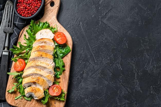 Petto di pollo grigliato. filetto di pollo e insalata di verdure fresche con pomodori e foglie di rucola. sfondo nero. vista dall'alto. copia spazio.