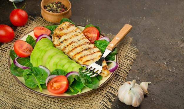 Petto di pollo alla griglia e insalata di verdure fresche con foglie di spinaci, avocado e pomodori su un tavolo scuro. uno stile di vita sano. dieta chetogenica. il concetto di dieta alimentare. copia spazio