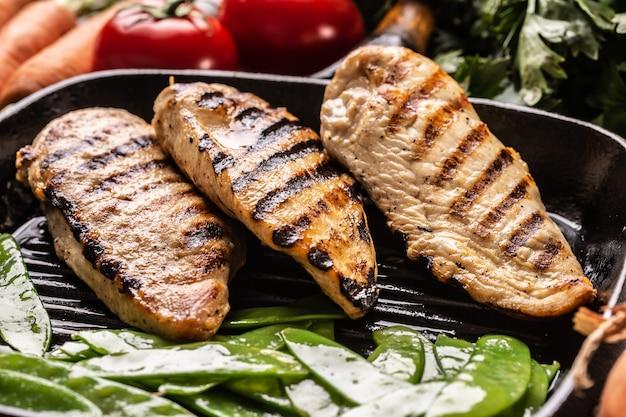 Petto di pollo alla griglia in padella con piselli dolci e verdure di condimento.