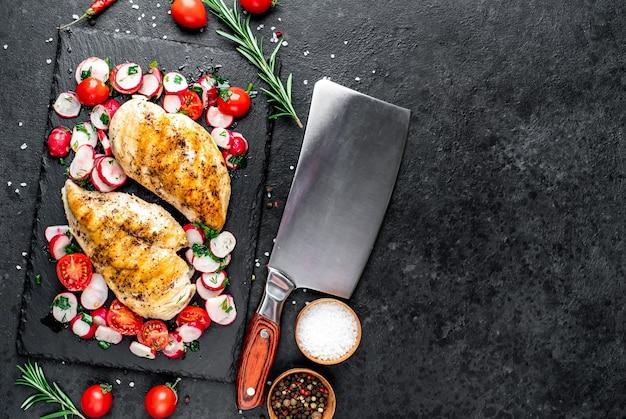 Petto di pollo alla griglia e insalata con verdure fresche pomodori e ravanelli carne di pollo con insalata cibo sano sul tavolo di pietra